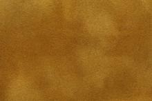 Background Of Dark Golden Suede Fabric Closeup. Velvet Matt Texture Of Yellow Nubuck Textile