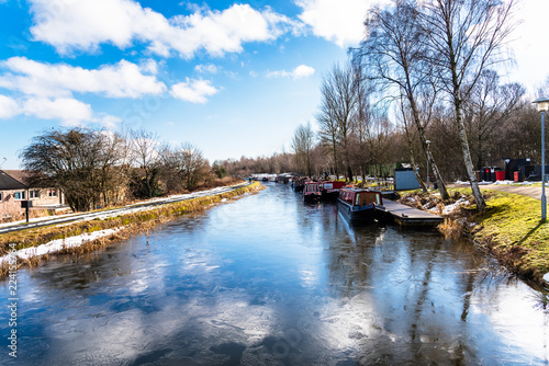 Spoed Foto op Canvas Kanaal Frozen Canal with Colourful Canal Boats Moored to Jetties under Blue Sky With Clouds on a Winter Day