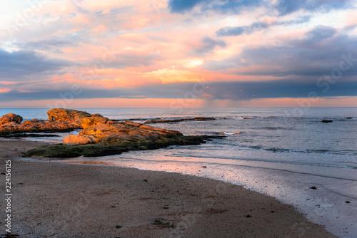 Orange Winter Sunset over a Deserted Sandy Beach with Sunlit Rocks. St. Andrews, Scotland