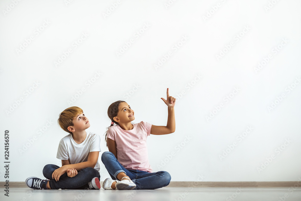 Fototapety, obrazy: The happy girl and a boy sitting on the floor and gesturing
