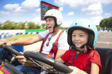 Father And Daughter Driving Go Kart On The Track