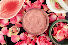 Pink Cosmetic Clay Closeup With Rose Petals, Ceramic Bowls On Black Table, Homemade Skincare Mask Preparation