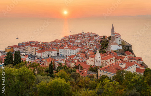 Foto  Romantic colorful sunset over picturesque old town Piran with sun on the background, Slovenia