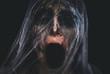 Leinwandbild Motiv Screaming creepy character covered with spiderweb on black background