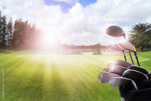 Photo  Golf clubs drivers over beautiful golf course at the sunset, sunrise time