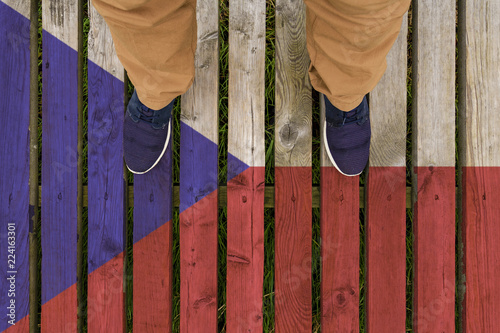 Photo  man stepped on a flag of Czech Republic painted on a wooden floor