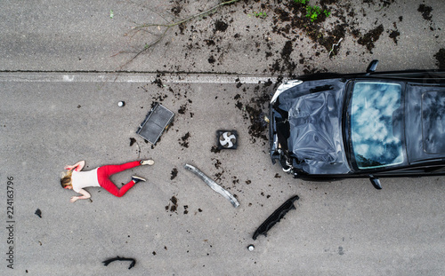 Obraz na płótnie Young injured woman lying on the road after a car accident, unconscious