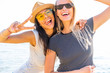 Image of two multiethnic girls 20s in stylish clothing laughing and enjoying summertime during beach party at seaside