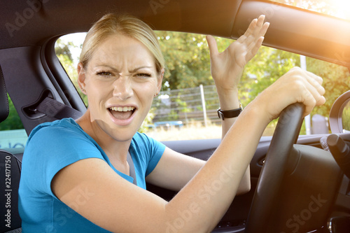 Fototapeta  Woman as a car driver is in stress and scolds of annoyance during the car ride