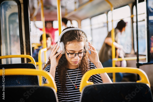Fotografie, Obraz  Curly girl in a bus with an earphones.