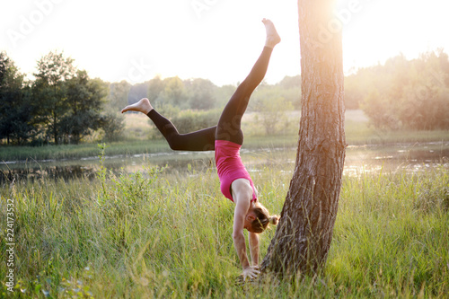 Sporty beautiful young woman doing handstand on a tree as a yoga exercise outdoo Fototapeta