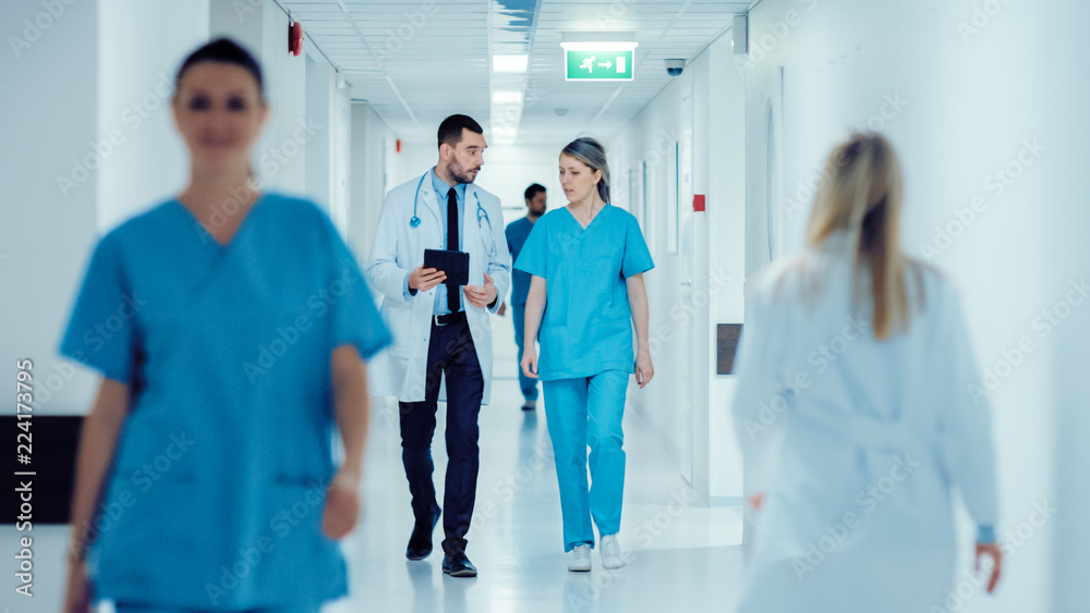 Fototapeta Surgeon and Female Doctor Walk Through Hospital Hallway, They Consult Digital Tablet Computer while Talking about Patient's Health. Modern Bright Hospital with Professional Staff.