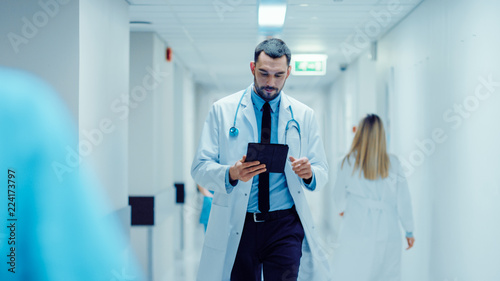 Determined Handsome Doctor Uses Digital Tablet Computer while Walking Through Hospital Hallway. Modern Bright Clinic with Professional Staff.