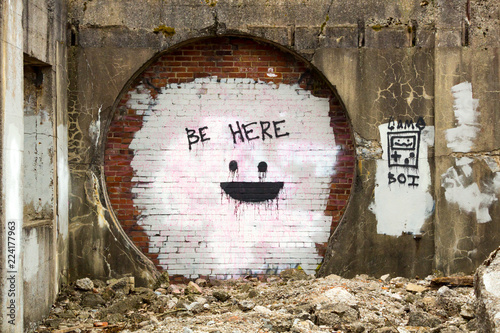 Photo  Old concrete wall with large round opening filled in with bricks and the message