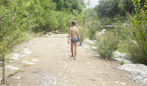 Boy walking barefoot on the river beach