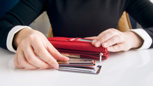 Closeup Photo Of Young Woman Putting Credit Cards In Leather Wallet