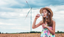 Cute Little Girl Making A Soap Bubbles In The Wheat Field. Childhood, Lifestyle Concept