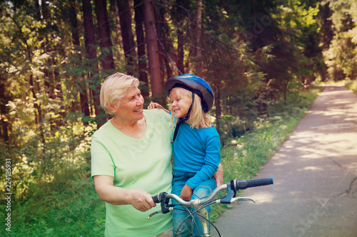 Photographie  grandmother teaching little granddaughter to ride bike