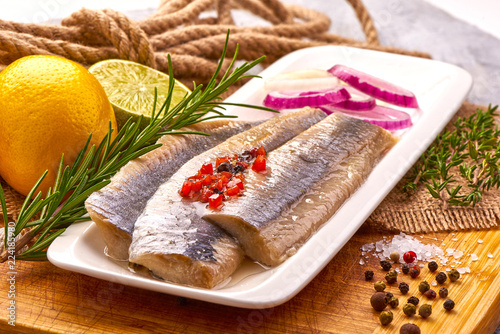 Fényképezés Atlantic Marinated herring fillet with pepper, tomatoes, herbs, onion and lemon on white plate on cutting board