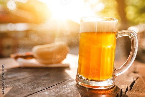 Photo sur Aluminium Biere, Cidre cold glass mug of beer with foam with bratwurst hotdog with sun beams