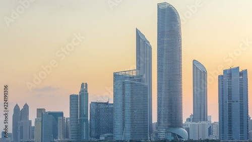 Poster Abou Dabi Abu Dhabi city skyline with skyscrapers before sunrise with water reflection night to day timelapse