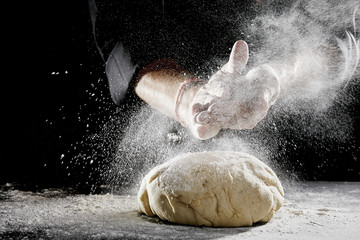 Man sprinkling white flour over blob of dough