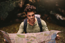 Male Hiker Using A Map To Loca...