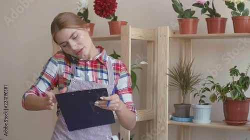 Small business. A girl in a plaid shirt and a striped apron stands with a paper tablet, enters the data into it with a ballpoint pen and accepts the order by phone. In the background, shelves with