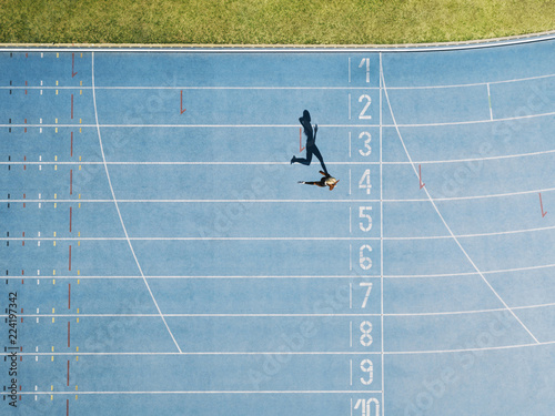 Fototapeta Track and field track with sprinter in overhead shot