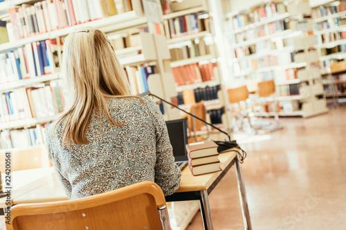 Foto  Junge blonde Frau sitzt in der Bibliothek und lernt für Examen