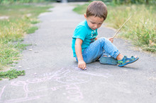 Cute Kid Boy Drawing With Chalk On The Pavement In The Park. Summer Activities For Children. Creative Child Drawing With Blue Chalk On The Road.
