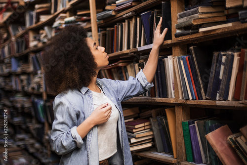 Fotografía  Young female african american librarian making order on bookshelves in college,