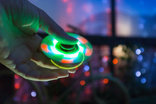Girl Playing With A Tri Fidget Hand Spinner Outdoors On Background Of A Night City. LED Glowing Hand Toy.