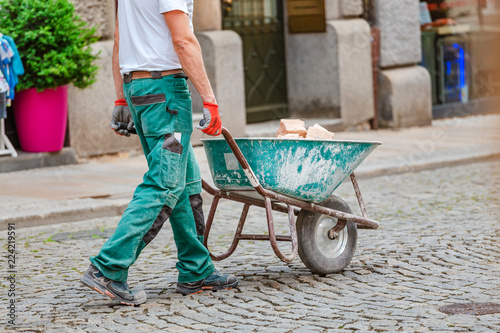 Photographie industrial worker with wheelbarrow cart full of bricks, job at construction site