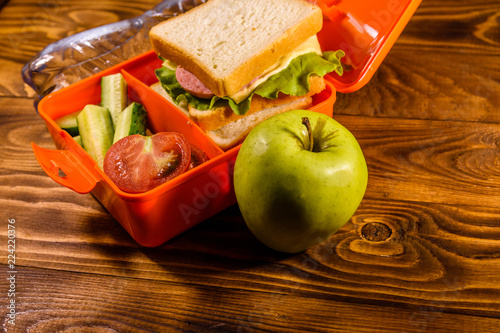 Bottle of water, green apple and lunch box with sandwich, cucumbers and tomatoes on wooden table