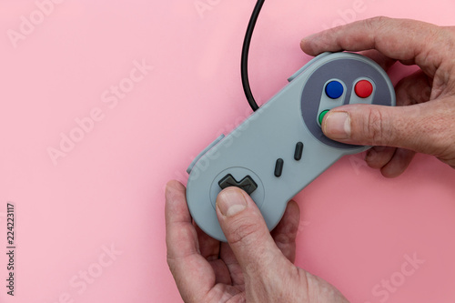 Fotografie, Obraz Man playing video game with controller pink background
