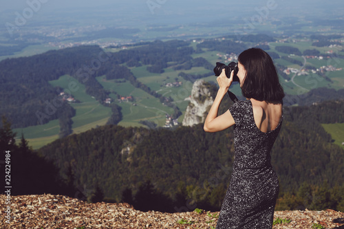 Photo  Brunette girl in a dress standing on the top of mountain and taking pictures with a camera