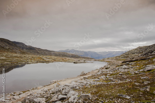 Rugged dramatic mountain landscape in norway cloudy dramatic day with calm lake