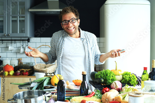 Fotobehang Koken Young guy tries to cook dinner at home