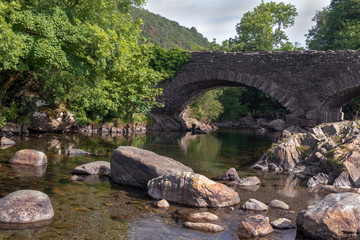 Fototapeta na wymiar Old stone bridge over River Duddon in Ulpha in the Lake District National Park, UK. Scenic view of English countryside on a sunny day