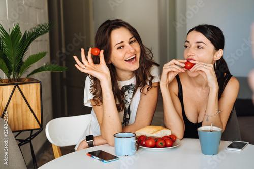 Fotografia  Two woman friends breakfast in the kitchen