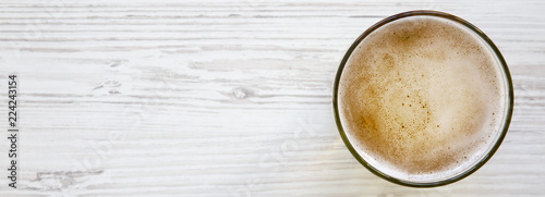 Glass of light beer on a white wooden surface. Copy space. Canvas Print