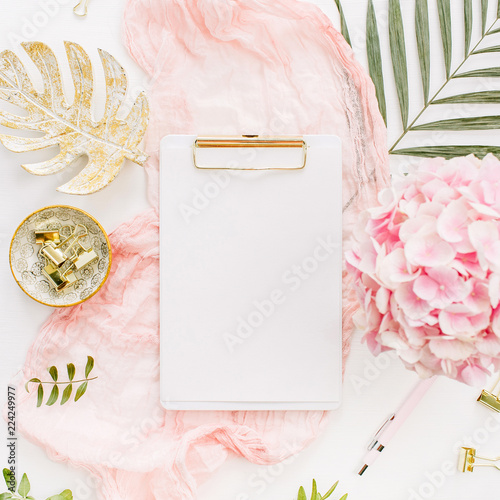 Cadres-photo bureau Roses Modern home office desk workspace with blank paper clipboard, pink hydrangea flowers bouquet, tropical palm leaf, pastel blanket, monstera leaf plate and accessories on white background. Flat lay.