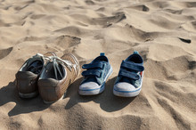 Close Up View On Abandoned Shoes And Yellow Sand