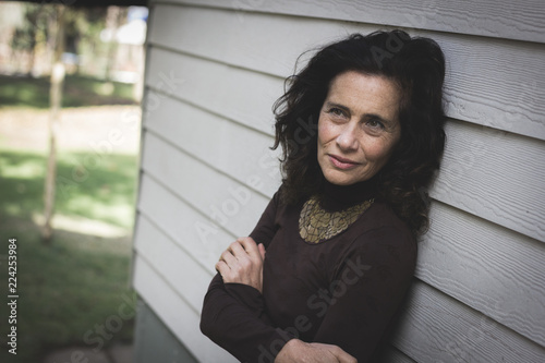 Fotografía  Thoughtful mature woman with crossed arms on chest leans on white wood plank wall