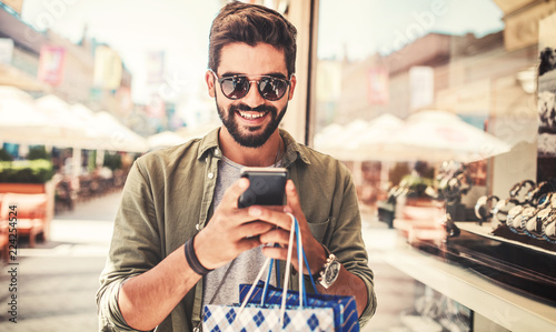 Shopping time. Modern young man with shopping bags making a phone call. Consumerism, shopping, lifestyle concept
