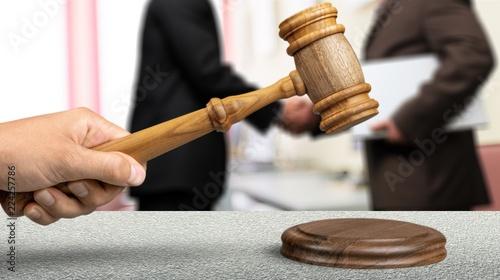 Photo Wooden judge hammer, handshake of business people
