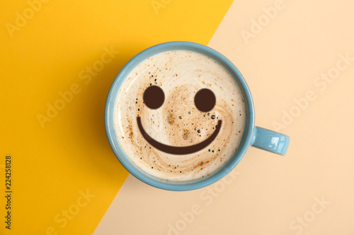 Cup of aromatic hot coffee on color background, top view