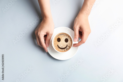 Young woman with cup of delicious hot coffee on light background, top view