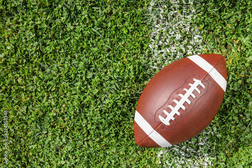 Ball for American football on fresh green field grass, top view. Space for text